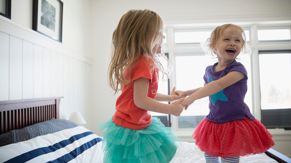 Playful sisters holding hands and jumping on bed. People, children, indoor, acoustics