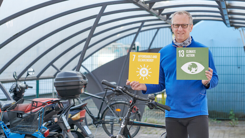 An employee holding Sustainable Development Goal #13: Climate Action and #7 Affordable and Clean Energy for the #iRockGlobalGoals campaign. Keywords: Keywords: Sustainable Development Goals, SDGs, Global Goals, Sustainability, Employees, Employee, Colleague, Colleagues